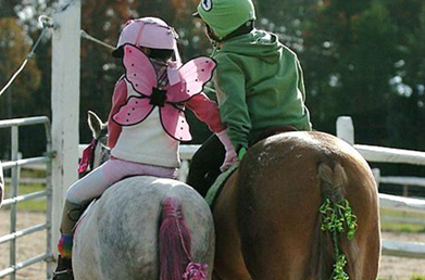 Two Young Ladies Riding into the Outdoor Arena